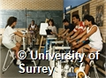 Photograph of students on exercise bikes in the weight training room in the sports hall at the University of Surrey